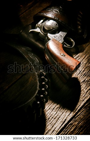 American West legend antique six-shooter revolver gun in vintage cowboy leather holster with old lead bullets on weathered wood plank western saloon table - stock photo
