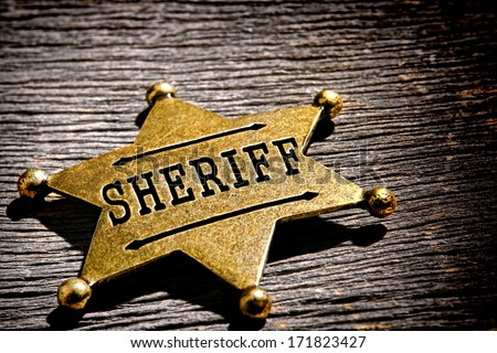 American West Legend law enforcement officer antique sheriff deputy star shape gold color brass badge as vintage western lawman identification and prestige shield on old frontier jail office table - stock photo