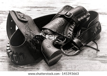 American West legend revolver style old six-shooter gun in antique cowboy leather holster on grunge aged wood planks - stock photo