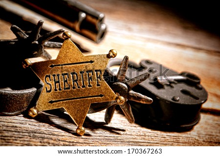 American West legend sheriff star badge lawman medallion with tools of the trade vintage western spurs and antique jail lock with old keys on an ancient wood jailhouse table  - stock photo