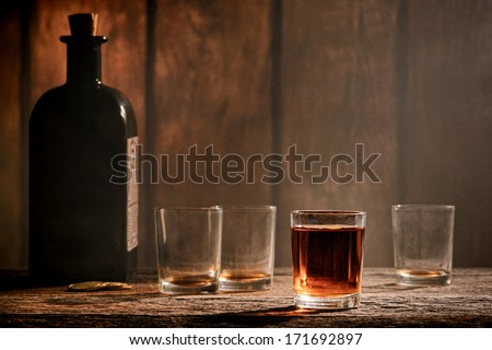 American West legend whiskey shot glass whisky drink and empty dirty alcohol glasses with antique whiskey bottle on an antique wood bar counter in a vintage Western saloon - stock photo
