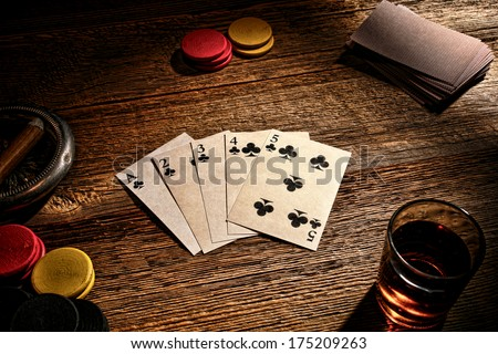 American West old gambler poker game with vintage playing cards showing a steel wheel straight flush hand on a weathered gambling wood table with wager tokens and whisky shot glass in a western saloon - stock photo