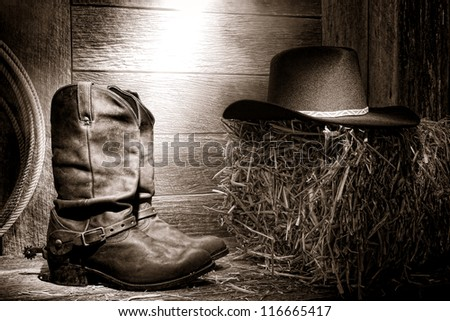 American West rodeo authentic leather roper boots and traditional western black felt hat on a bale of straw - stock photo
