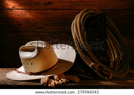American West rodeo cowboy authentic white straw hat and traditional rancher gloves with lariat lasso on vintage roper western boots on aged weathered barnwood floor in an old ranch barn - stock photo