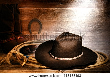 American West rodeo cowboy black felt hat on an authentic Western roping lariat lasso with leather riding boots on weathered wood floor in an old ranch barn - stock photo