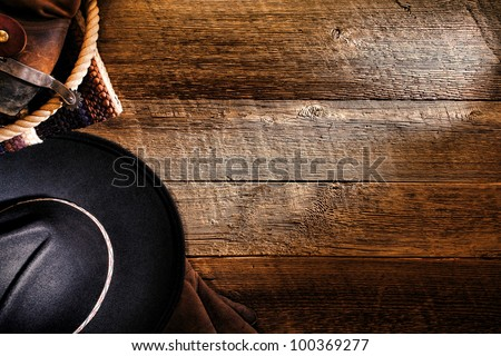 American West rodeo cowboy black felt hat with tools of the trade and authentic brown leather western boots with spur on old weathered ranch barn wood floor as a grunge background - stock photo