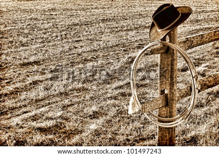 American West rodeo cowboy hat and authentic lariat lasso on a fence end post in a ranch  field in vintage nostalgic sepia - stock photo