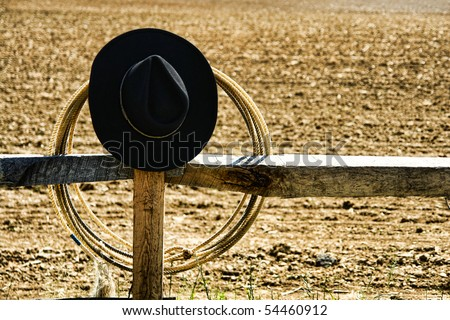 American West rodeo cowboy hat and lasso on a wood post fence near a ranch dusty earth field 