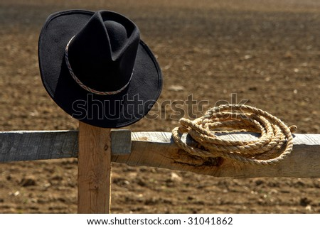 American West rodeo cowboy hat and rancher rope on a wood post fence near a dusty ranch field 