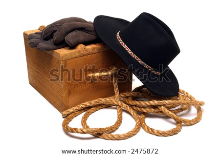 American West rodeo cowboy hat and traditional ranch tools with gloves and rope on an antique wood box