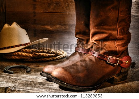 American West rodeo cowboy pair of traditional leather roper style western riding boots with authentic ranching spurs with hat and rope on an antique wood floor in an old ranch aged wooden barn - stock photo
