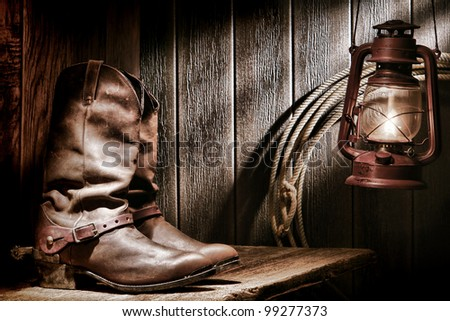 American West rodeo cowboy traditional leather roper boots with authentic Western riding spurs on an old wood bench in a vintage ranch barn lit by a nostalgic kerosene oil lamp - stock photo