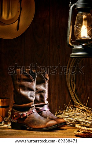 American West rodeo cowboy traditional leather working roper boots with authentic Western riding spurs in a vintage ranch barn with ranching tools lit by an old nostalgic kerosene oil lantern - stock photo