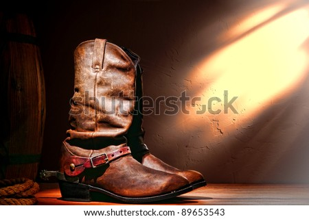 American West rodeo cowboy traditional leather working roper boots with authentic Western riding spurs in a vintage ranch barn - stock photo