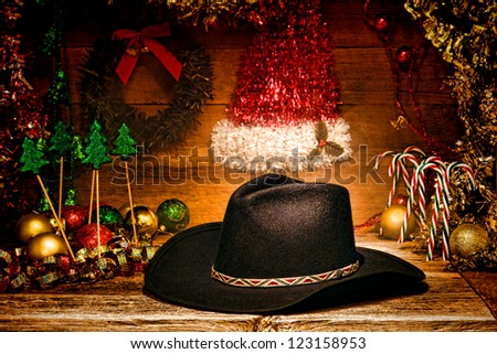 American West rodeo traditional black felt cowboy hat on wood vintage shelf with festive Christmas display decoration in authentic country and western motif for a nostalgic Christmastime greeting card - stock photo