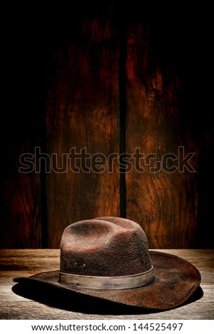 American west rodeo used and worn brown felt hat with dirty band on old wood plank in a weathered wooden barn - stock photo