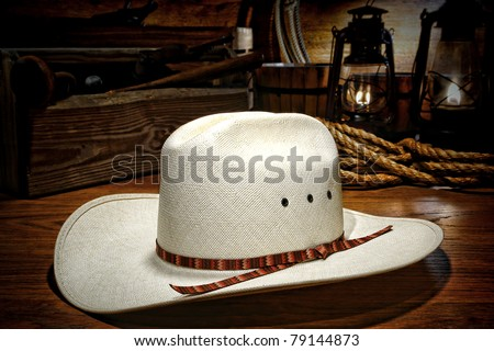 American west rodeo white straw cowboy hat on wood planks in a rustic ranch barn with old kerosene lamps burning and traditional western ranching tools - stock photo