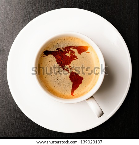 Americano. cup of fresh espresso on table, view from above. Earth silhouette is from visibleearth.nasa.gov - stock photo