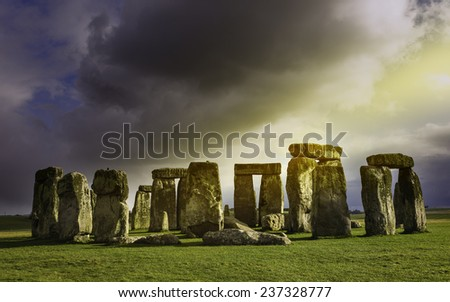 AMESBURY, UK - MARCH 03: Stonehenge, prehistoric monument, set against a foreboding sky and a blue sunny at Amesbury, Wiltshire, UK. - stock photo