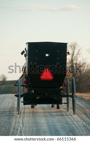 Amish buggy with a horse riding on gravel rural road - stock photo