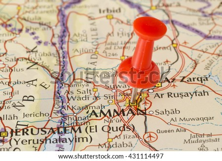 Amman marked on map with red pushpin. Selective focus on the word Amman and the pushpin. Pin is in an angle. Midground is sharp while foreground and background is blurry. - stock photo