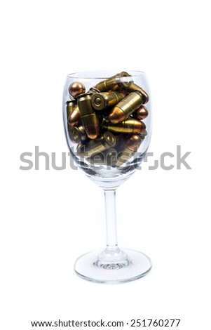 Ammunition in a wine glass. - stock photo