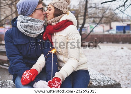 Amorous couple with Bengal light kissing in winter park - stock photo