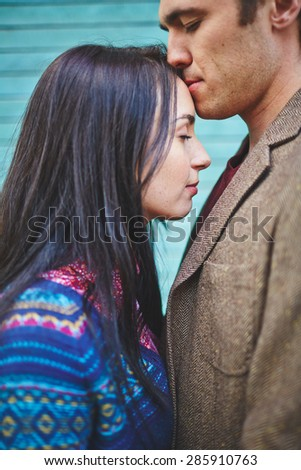 Amorous man kissing his girlfriend on forehead - stock photo
