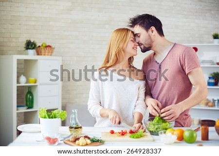 Amorous young couple cooking in the kitchen - stock photo