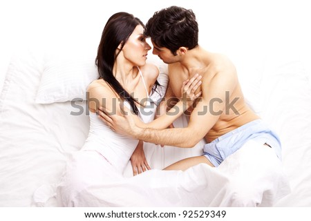 Amorous Young Couple. Young couple in love holding each other in bed in anticipation of a kiss. - stock photo