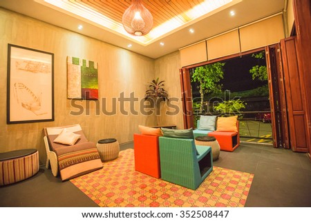 AMPAWA, THAILAND - DECEMBER 15: The living room interior design with sofa, armchair and colorful pillows in famous vintage hotel at ancient Ampawa, Thailand on December 15, 2015. - stock photo
