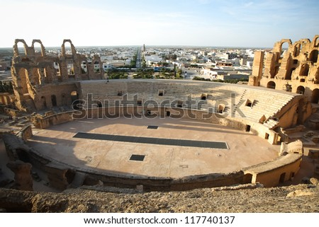 Amphitheatre with El Djem city skyline. Central podium of roman biggest amphitheater in africa with city skyline of El Djam in the background, Tunisia - stock photo