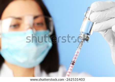 Ampule and syringe in hands of doctor on blue background - stock photo