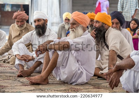 AMRITSAR, INDIA - SEPTEMBER 28, 2014: Unidentified Sikhs men visiting the Golden Temple in Amritsar, Punjab, India. Sikh pilgrims travel from all over India to pray at this holy site. - stock photo