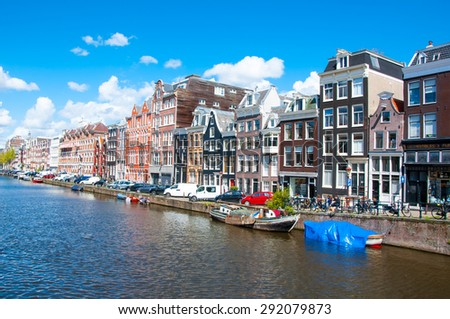 AMSTERDAM-APRIL 30: Amsterdam cityscape with row of cars, bikes and boats parked along the Singel canal on April 30,2015, the Netherlands. - stock photo
