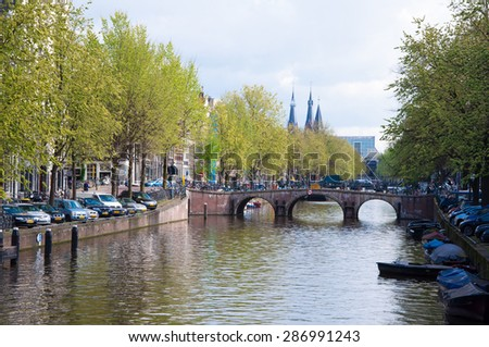 AMSTERDAM-APRIL 30: Amsterdam cityscape with row of cars parked along the canal on April 30,2015, the Netherlands.  - stock photo