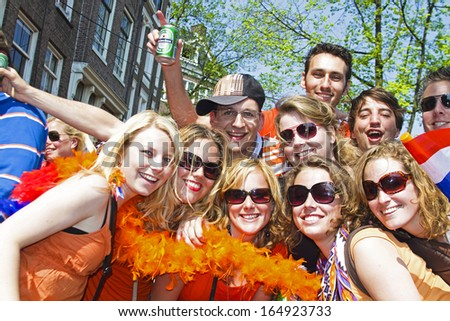 AMSTERDAM - APRIL 30: Group of friends in orange partying at the celebration of queensday on April 30, 2011 in Amsterdam, The Netherlands - stock photo