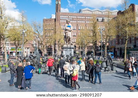 Amsterdam-April 30: Rembrandtplein with sculptures of the Night Watch by Russian artists Mikhail Dronov and Alexander Taratynov, tourists go sightseeing on April 30, 2015, the Netherlands. - stock photo