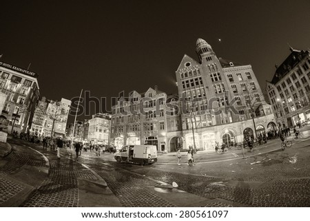 AMSTERDAM - APRIL 25, 2015: Tourists and locals in Dam Square at night. The city attracts almost 10 million people annually. - stock photo