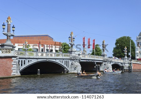 AMSTERDAM-AUG. 19: Ancient bridge with opera house on Aug. 19, 2012 in Amsterdam. It is known as Venice of the North, its beautiful canal belt was added to world heritage list in July 2010. - stock photo