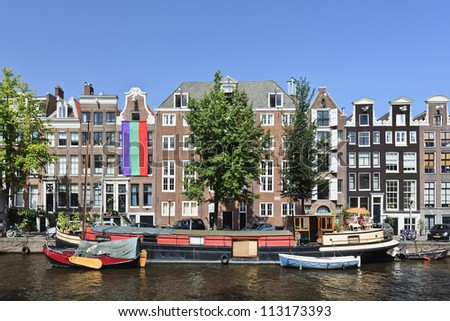 AMSTERDAM-AUG. 19, 2012. Houseboat on Aug. 19, 2012 in Amsterdam. There are around 2,500 house boats along 165 canals where locals live. The canal belt was added to world heritage list in July 2010 - stock photo