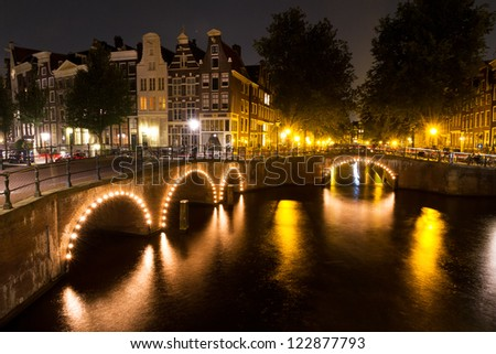 Amsterdam canal at night with lights on the bridges - stock photo