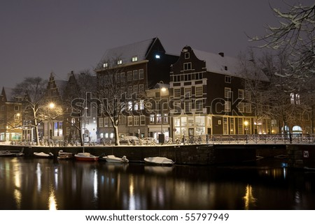 Amsterdam canals and typical houses on a snowy winters night - stock photo