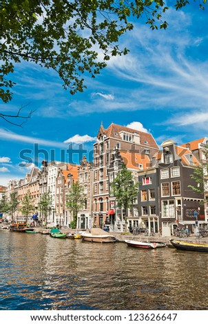 Amsterdam canals and typical houses with summer sky - stock photo