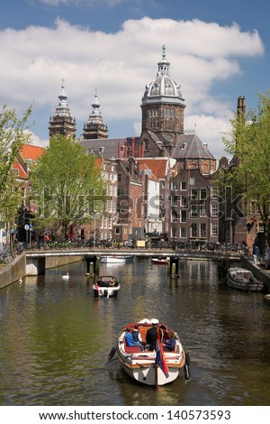 Amsterdam city with boats on  canal in Holland - stock photo