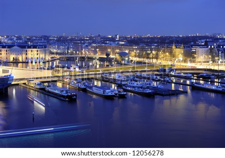 Amsterdam harbor at night, with traffic racing through the streets, and lights illuminating the various historic buildings - stock photo