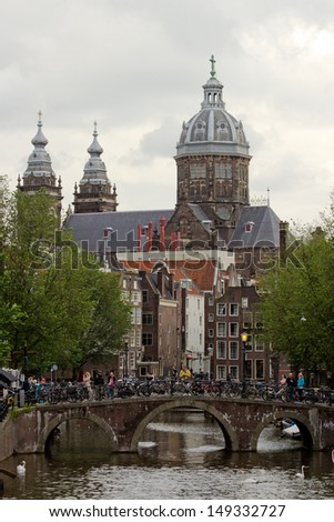 AMSTERDAM, HOLLAND-JULY 27: Canal and bridge on July 27, 2012 in Amsterdam. It is known as Venice of the North, its canal belt was finally added to the world heritage list in July 2010.  - stock photo