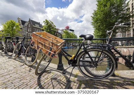 AMSTERDAM, HOLLAND - JUNE 19, 2015: A typical dutch bicycle with a wood basket, parked at a bridge on a sunny day. - stock photo