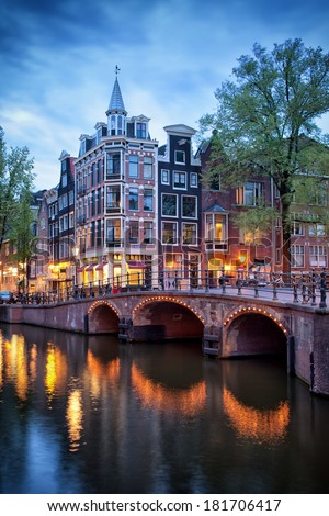 Amsterdam in the evening, old houses and bridge over canal, corner of Grimburgwal and Oudezijds Voorburgwal, North Holland, Netherlands. - stock photo