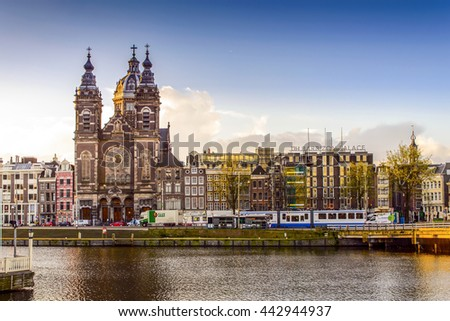 AMSTERDAM, NETHERLANDS - APRIL 7: View of St. Nicolas Church along the river in Amsterdam on April 7, 2016. It is the city's major Catholic church. - stock photo